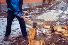 Man with a axe in his hand in the process of cutting wood Royalty Free Stock Image