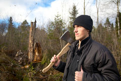 Man with an axe looks at the tumbled down wood Stock Photography