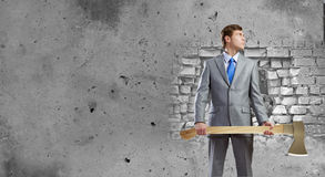 Man with axe. Young determined businessman with axe in hands Royalty Free Stock Image