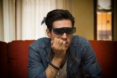 Man bärande exponeringsglas som 3d sitter hålla ögonen på en video Arkivbilder