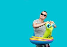 Man bärande solglasögon, den randiga skjortan som simmar varvar i form av en snigel som bort ser, blå bakgrund semester Royaltyfria Foton