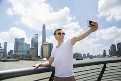 Man bärande solglasögon, medan ta selfie mot Pudong horisont Arkivbild