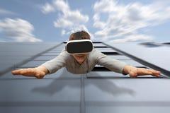 Man bärande virtuell verklighetexponeringsglas som flyger från en skyskrapa Arkivbilder