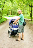 Man with baby buggy Stock Image