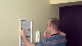 Man with baby girl on hands turning on circuit breakers at power control panel at home stock video footage