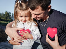 Man and baby holding a two red plastic heart. father hugs the daughter.  stock image