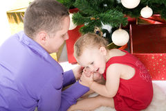 Man with baby under christmas tree Stock Image