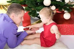 Man with baby under christmas tree Stock Photos