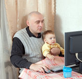 Man with  baby working Royalty Free Stock Photos