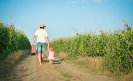 Man and babygirl walking away on road between corn Stock Images