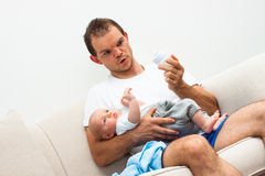 Man babysitting. Portrait of a men going to feed baby boy royalty free stock photography