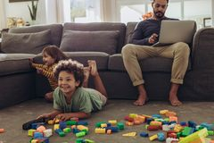 Man babysitting his kids and working from home. Man working on laptop sitting at home with kids playing on the floor. Cheerful kids playing with building blocks stock photos