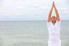 Man at the bach doing yoga Stock Images