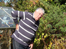 Man back ache or pain. An elderly man with very bad back pain, leaning forward and holding his back stock image
