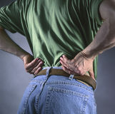 Man with back pain. Man holding back in pain Royalty Free Stock Photography
