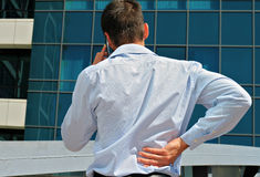 Man with  back pain. Business man rubbing his painful low back Stock Image
