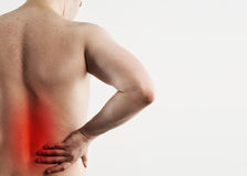 Man back pain. Closeup of male body with red spot o painful zone. Young man suffering from lumbago. Back injury and treatment Stock Images