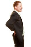 Man with back pain holding his hands on his back. In business clothing Stock Photos