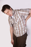 Man with back pain. A man in hunched position due to back pain Stock Photo