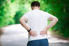 Man with back pain, kidney inflammation, trauma during workout. Outdoors concept royalty free stock image