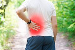 Man with back pain, kidney inflammation, trauma during workout. Outdoors concept stock photos