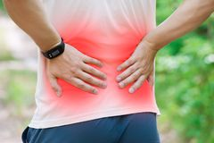 Man with back pain, kidney inflammation, trauma during workout. Outdoors concept stock photo
