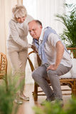 Man with back pain. Senior men with back pain and his helpful loving wife Stock Image