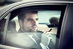 Man in the back seat of a car smoking Stock Images