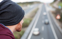 Man back at the top of a bridge over a highway Royalty Free Stock Image