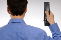 Man back using remote. Man in a shirt using remote control Royalty Free Stock Photo