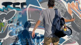 A male graffiti artist adds another spray paint to a graffiti wall. A man in a back view comes to a wall and sprays it with paint stock video