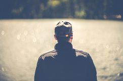 Man back view portrait looking to water stock photography