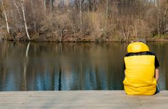 A man from the back in a yellow vest sitting on a platform near the pond.  Stock Images