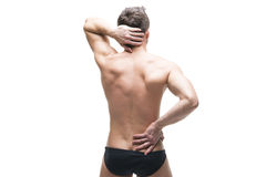Man with backache. Pain in the human body. Muscular male body. Isolated on white background. Middle part of the body Royalty Free Stock Photo