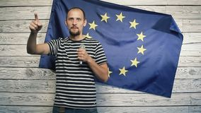 A man on the background of the EU flag says it. Politician on the background of the flag of the European Union says it in the hands of a microphone stock video footage