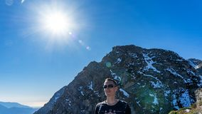 Man on the background of Peak of the Achisho mountain covered by snow and sun flares, winter in Sochi, Russia stock photo