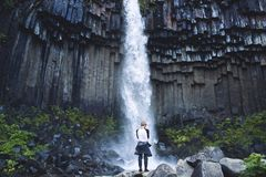 Man on background of Svartifoss waterfall surrounded by basalt columns in the south of Iceland Stock Photo