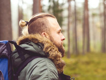 Man with a backpack and beard hiking in the forest. Camp, adventure, traveling concept. Man with a backpack and beard hiking in forest. Autumn color and hipster royalty free stock images