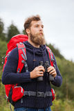 Man with backpack and binocular outdoors. Adventure, travel, tourism, hike and people concept - man with red backpack and binocular outdoors Stock Photo