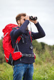 Man with backpack and binocular outdoors Stock Photo