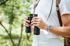 Man with backpack and binoculars in forest Royalty Free Stock Image