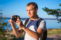 Man with backpack and camera on the beach Stock Images