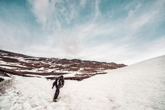 Man with a backpack in camouflage rises to the top of the mountain. A man in military clothes rises to the mountains on the way in the summer. man in the snow Stock Photography
