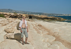 Man with backpack in cap standing on rock looking at sea. Man in cap,  standing on rock looking at sea, cyprus Stock Photo