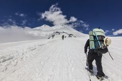 Man with backpack climbing on elbrus in snowy caucasus mountains royalty free stock image