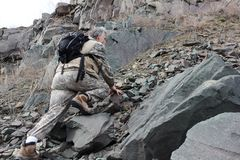Man with a backpack climbing on stones to the mountain Stock Photography