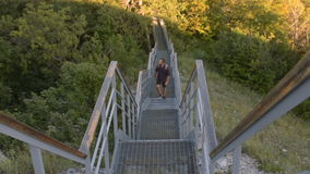 Man with backpack climbs the stairs in the mountains. stock footage