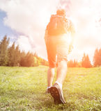 Man with backpack climbs up to the  hill Royalty Free Stock Photo