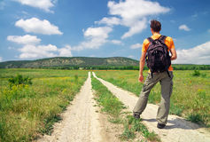 Man with a backpack on a country road. Man tourist. Royalty Free Stock Image