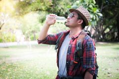 Man with backpack drinking water from bottle in woodland stock photos